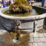 Fontaine en haut du bourg : l'eau se jette dans le collecteur en fonte à tête de lion