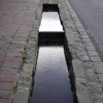 Le Fil de l'eau le long du trottoir en gros plan , grande rue à BLangy le Château